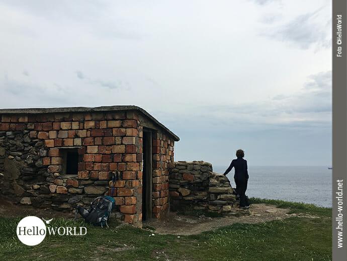 Das Bild, bei der zweiten Camino del Norte Etappe in der Nähe von Pobena aufgenommen, zeigt eine alte steinerne Ruine an der Steilklippe, vor der eine Frau ins Meer blickt.