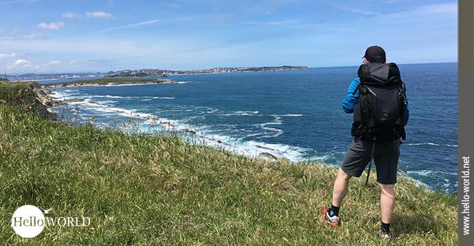 Das Bild zeigt einen Mann mit Rucksack an den Steilklippen der spanischen Nordküste stehen und Richtung Santander blickend bei blauem Himmel.