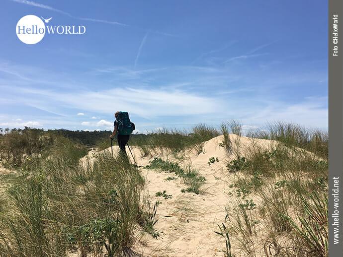 Das Bild einer Dünenlandschaft an der spanischen Nordküste zeigt eine Frau mit Rucksack und Stöcken bepackt, wie sie über die Sandhügel geht.