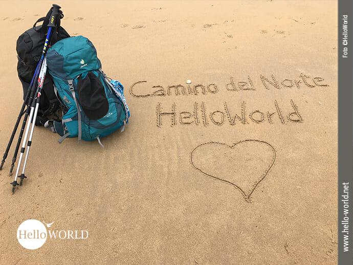 Das Bild zeigt zwei Rucksäcke am Strand stehend und daneben die Worte Camino del Norte und HelloWorld mit einem Herz in den Sand gemalt.