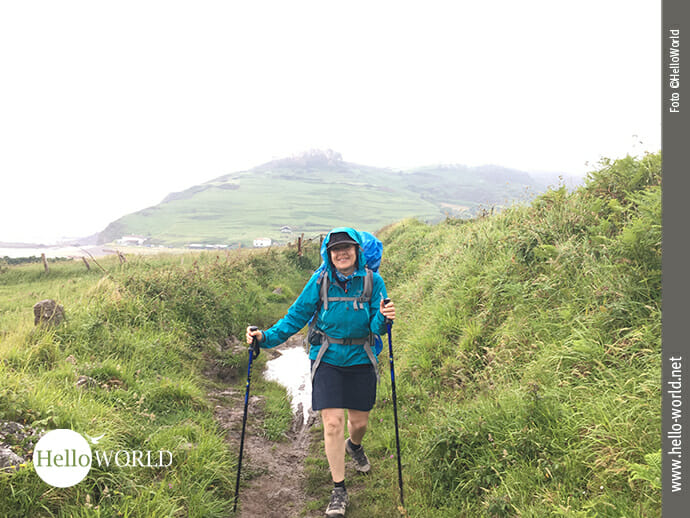 Das Bild zeigt eine Frau auf einem schmalen Küstenweg, die bei Regen entlang der spanischen Nordküste wandert.