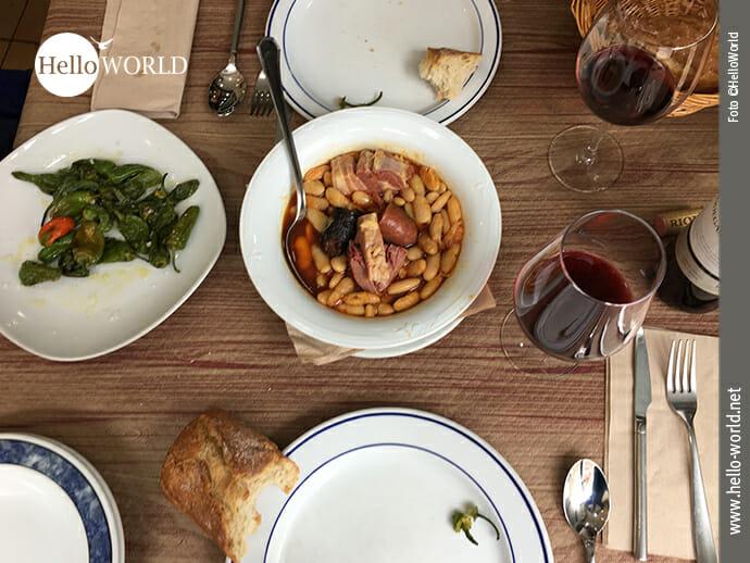 Das Bild, entstanden in einer Sidreria an der spanischen Nordküste, zeigt eine Tisch mit Geschirr und Gläsern, auf dem der für Asturien typische Bohneneintopf steht.