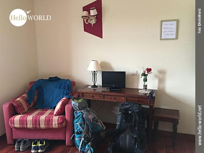 Das Bild zeigt ein Hotelzimmer an der spanischen Nordküste mit zwei Rucksäcken und Schuhen.