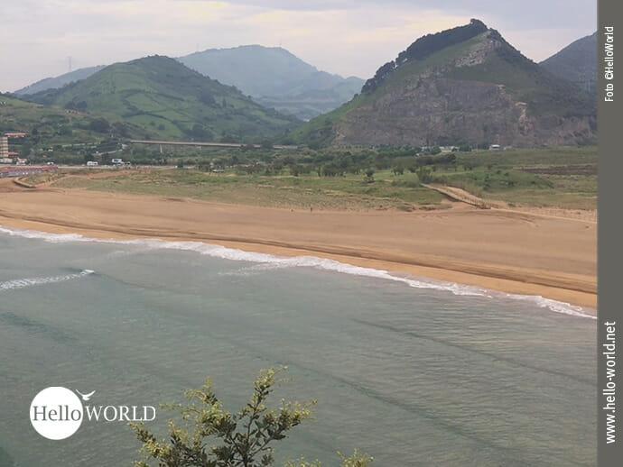 Das Bild vom Playa de la Arena an der spanischen Nordküste zeigt den Blick auf den Strand, im Vordergrund der Atlantik, dahinter eine bergige Landschaft.