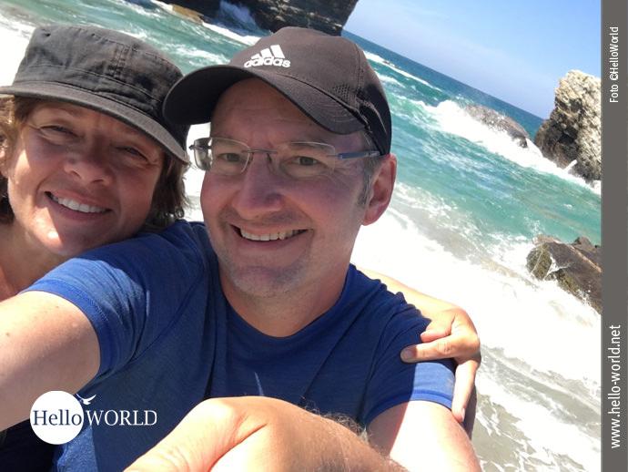 Dieses Bild an der spanischen Nordküste zeigt ein Selfie von Andrea und Nico vor einer Traumkulisse mit türkisfarbenen Meer, weißem Strand und Felsen im Hintergrund.