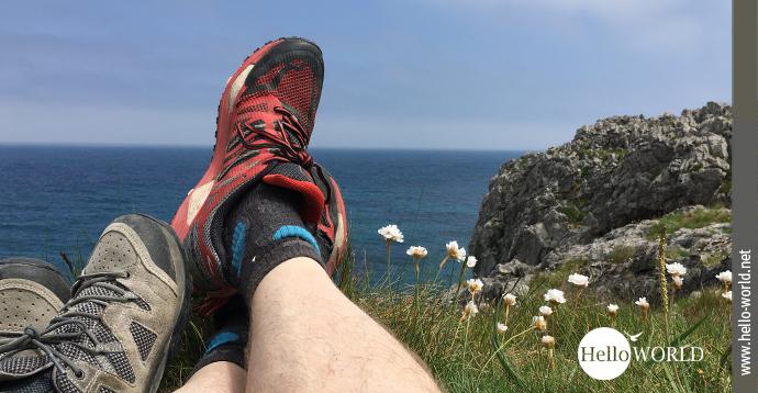 Das Bild von der spanischen Nordküste zeigt zwei paar Beine mit Wanderschuhen, die auf Felsen liegen. Dahinter das Meer und der Himmel.