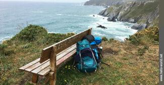 Das Bild von der spanischen Nordküste zeigt eine Holzbank am Rande einer Steilklippe, zwei Rucksäcke, dahinter der Atlantik.