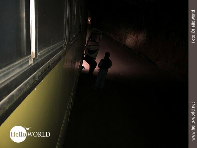 Das Bild aus Bolivien zeigt die Seite eines Busses, der in der Dunkelheit auf einer Straße liegengeblieben ist.