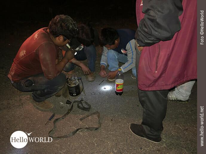 Das Bild aus Bolivien zeigt drei Männer, die in der Dunkelheit auf der Straße knien und versuchen mit Gummiresten und Colaflasche etwas zu reparieren.