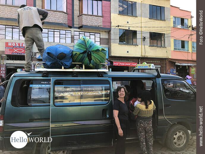 Das Bild aus Bolivien zeigt Andrea in Coroico vor einem Minibus stehend, auf dessen Dach ein Mann große Säcke befestigt.