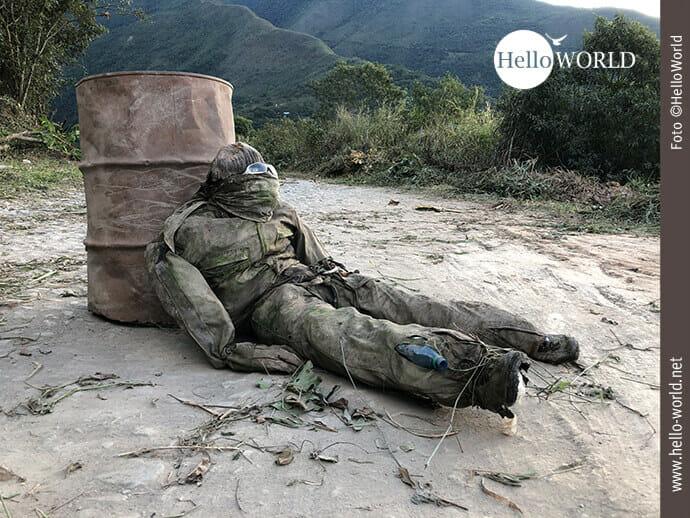 Dieses Bild aus Bolivien in der Nähe des El Camino de la Muerte zeigt ein uniformierte Puppe, die den Tod widerspiegelt und an einer alten verrosteten Tonne liegt.
