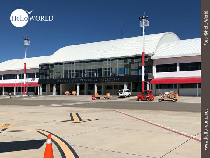 Hier sieht man das weiß-rote Flughafengebäude Alcantari in Südamerika, Bolivien, das auf über 3.000 Metern Höhe liegt bei strahlend blauem Himmel.