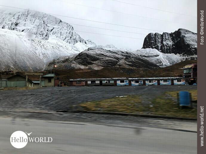Dieses Bild aus Bolivien zeigt den Blick aus dem Bus auf die verschneiten Berge und auf einige Hütten auf 4.600 Metern Höhe.