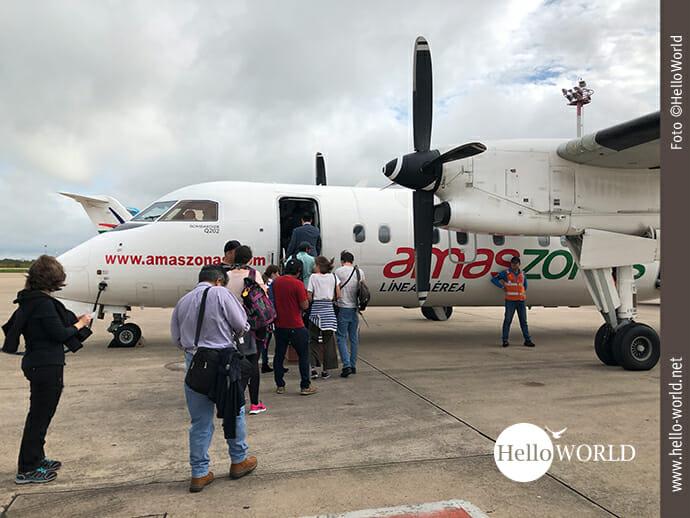 """Das Bild, aufgenommen auf einem Flughafen in Südamerika, zeigt eine Propellermaschine mit dem Schriftzug """"amaszona"""", in die die Passagiere einsteigen."""