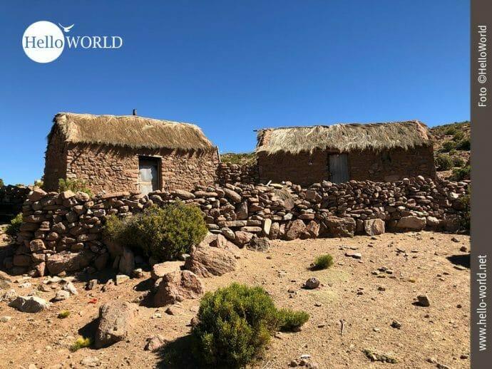 Das Bild aus Südamerika, Bolivien, zeigt zwei kleine Steinhütten mit Strohdach und einer Steinmauer davor.