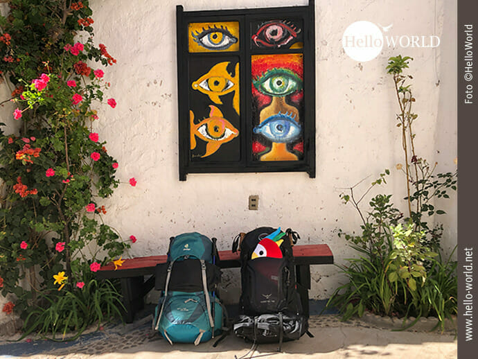 Dieses Bild aus Bolivien zeigt unsere gepackten Rucksäcke im Hof unserer Unterkunft vor einem bunten Bild.