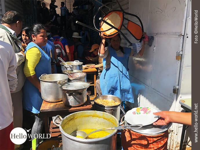 """Auf dem Bild aus Sucre, Südamerika, sieht man wie Mitarbeiter der """"Comidas de Mercados"""" die Utensilien aus der Markthalle auf den Bürgersteig tragen und eine Essensausgabestation aufbauen."""