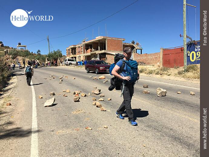 Das Bild zeigt einen Mann mit Rucksack, der durch ein Streikgebiet in Südamerika geht.
