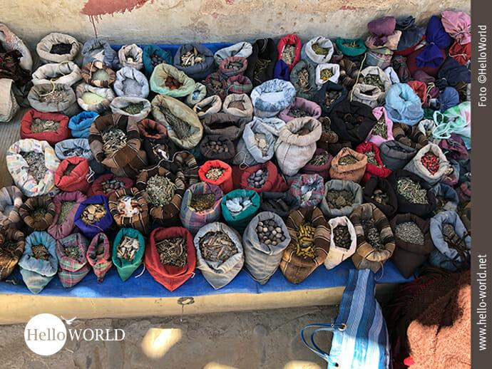 Das Bild vom Sonntagsmarkt in Tarabuco, Bolivien, zeigt einen Stand mit unterschiedlichsten Heilmitteln aus der Natur, verpackt in kleine bunte Säckchen.