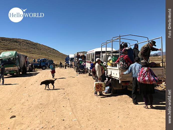 Das Bild aus Südamerika zeigt eine sandige Straße am Ortsrand von Tarabuco auf der Lastwagen und Busse parken, im Vordergrund steigen Marktbesucher von einem Fahrzeug.