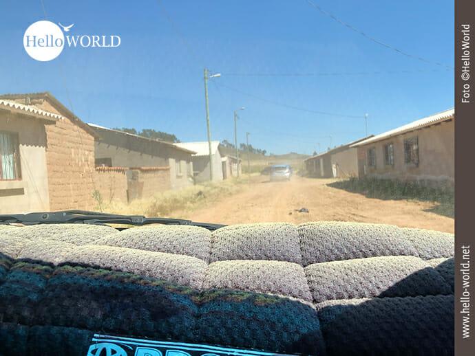 Das Bild wurde in Südamerika, Bolivien, aufgenommen und zeigt den Blick aus der Vorderscheibe eines Taxis, das auf einer sandigen Straße an Häuserreihen entlang fährt.