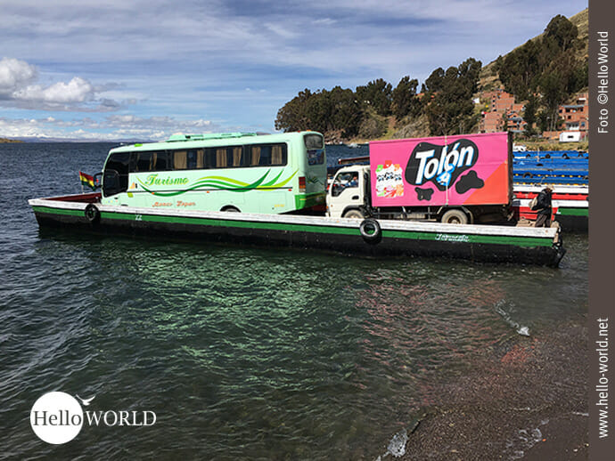 Dieses Bild am Ufer des Titicacasees in Bolivien zeigt ein Fährfloss mit einem Buss und einem Kleintransporter beladen.