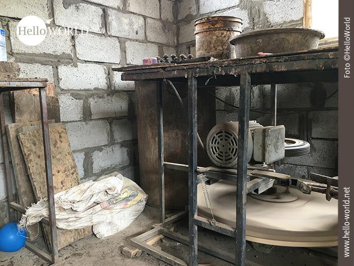 Das Bild aus Ecuador zeigt eine Nahaufnahme einer Werkbank für Töpfer mit einem elektrischen Motor.