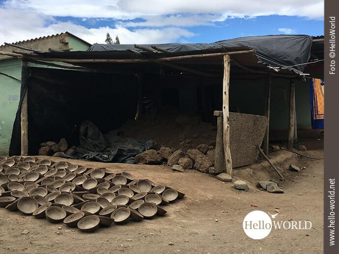 Das Bild aus Ecuador zeigt einen Verschlag am Straßenrand in dem sich Erde häuft, davor liegen Schalen aus Ton zum Trocknen aus.