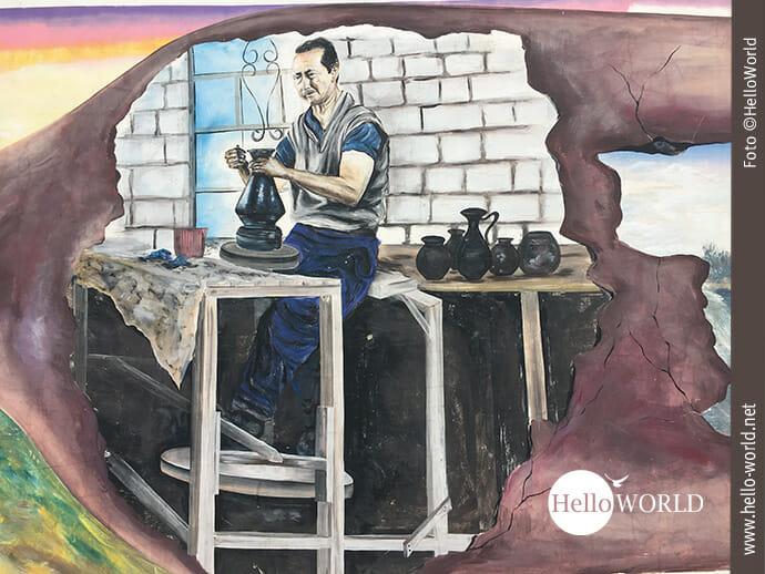 Dieses Bild aus Ecuador zeigt eine Wandmalerei in La Victoria auf der ein Mann vor seiner Töpferscheibe steht und gerade ein Vase anfertigt.