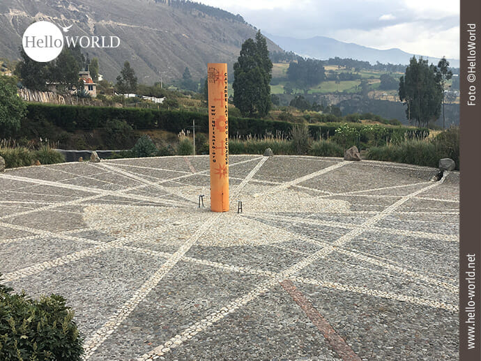 Dieses Bild aus Ecuador zeigt das Äquatordenkmal Quitsato mit seiner orangefarbenen Säule, die auf einem großen gepflasterten Platz steht.