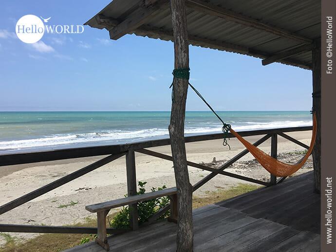 Das Bild aus Ecuador zeigt einen Strand mit Blick auf das Meer, im Vordergrund eine hölzerne überdachte Terrasse mit einer orangenen Hängematte.