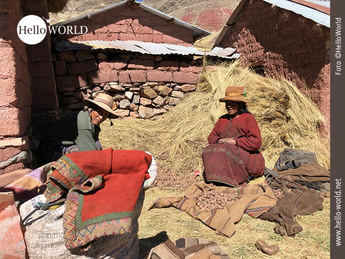 Dieses Bild aus Peru wurde im Palccoyo Gebiet aufgenommen und zeigt ein älteres mit Hüten bekleidetes Bauernpaar, das im Hof auf Stroh sitzt, davor Kartoffeln.