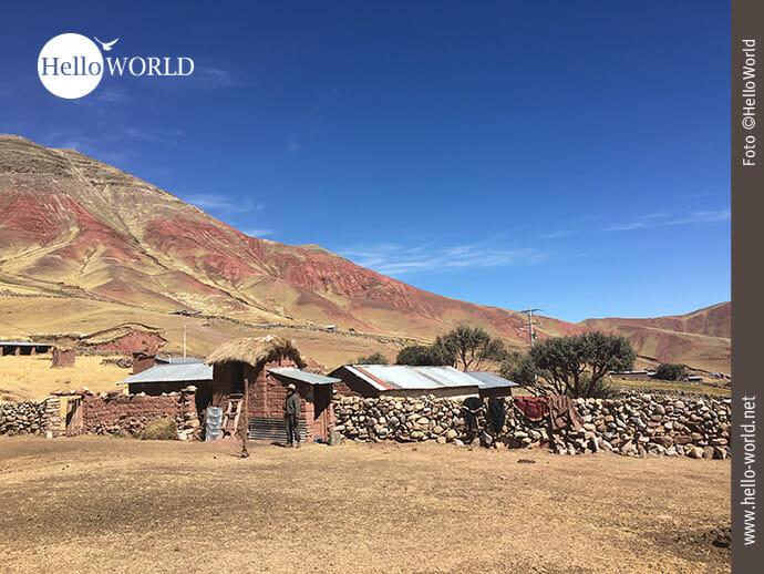 Dieses Bild stammt aus dem Red Valley in Peru und zeigt ein kleinbäuerliches Anwesen, vor dem ein Mann mit Hut steht, dahinter die rötlichen Berge.