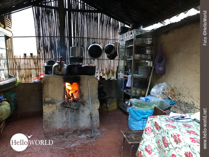 Dieses Bild zeigt den Blick in eine Küche im Colca Canyon, Peru, in der Mitte ein Steinofen, in dem Feuer brennt, darüber hängen Töpfe.