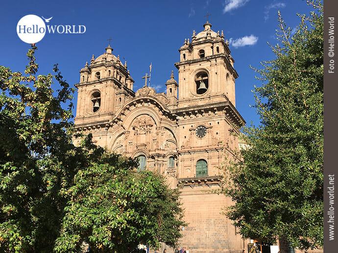Dieses Bild aus Cusco, Peru, zeigt die Glockentürme der Iglesia la Compania de Jesus, im Vordergrund Bäume.