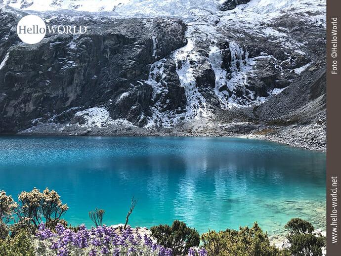 Dieses Bild aus Nordperu zeigt den Blick auf die tieftürkisfarbene Lagune 69, dahinter graues, schneebedecktes Gestein.