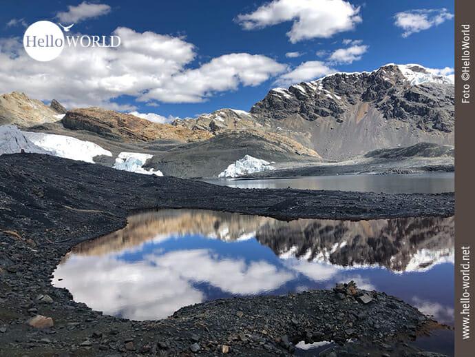 Dieses Bild aus Nordperu zeigt den Blick auf den Pastoruri Gletscher, der sich bei blauem Himmel im Wasser spiegelt.
