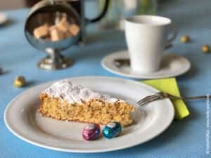 Das Bild zeigt eine Kaffeetafel mit einem Stück Tarta de Santiago, gebacken nach Originalrezept.