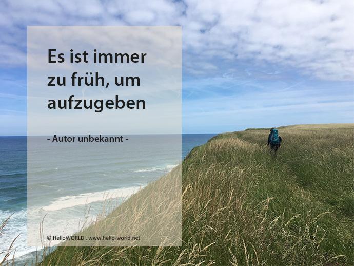 Hier sieht man eine Wanderin durch Gras an der Küste entlang gehen, im Vordergrund ein Motivations-Zitat.